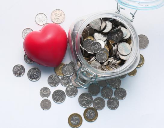 Madeni paralarla dolu bir kavanoz ve kırmızı bir kalp ile temsil edilen vergi kredisi bağışları